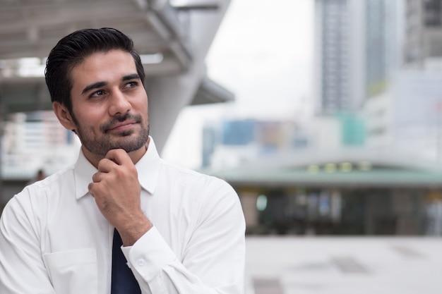 思いやりのあるアジアのビジネスマンが考えて見上げる。アジア、北インドの成功した自信のあるビジネスマンの肖像画思考、計画、見て、将来のプロジェクトを持つ