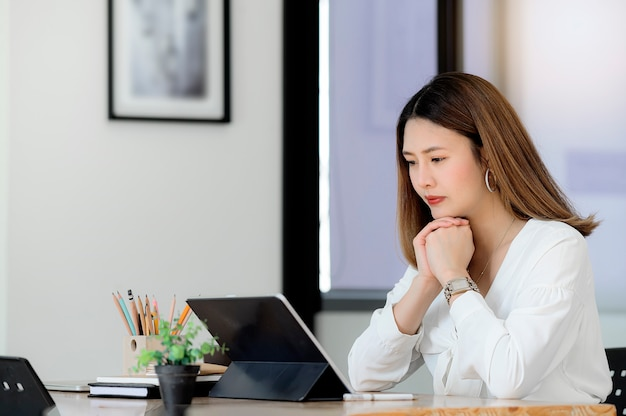 Thoughtful asian businesswoman with hands on chin looking at tablet screen and thinking solving at work.
