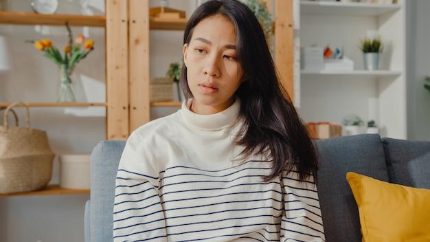 Задумчивая азиатская дама сидит, чувствуя себя одинокой, чувствуя себя подавленной и проводя время в одиночестве, оставаясь дома