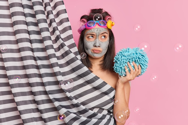 Thoughtful asian woman applies clay mask makes hairstyle with hair rollers holds shower sponge has deep thoughts while taking douche poses behind curtain poses against pink studio background