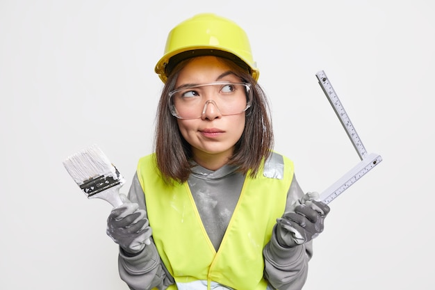 Thoughtful asian woman construction engineer in uniform holds tape measure for measuring layout and brush ready to work at building something stands against white wall. industrial worker