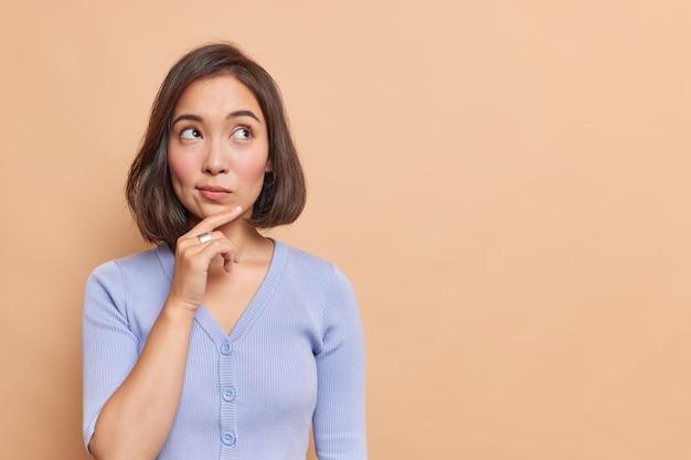 思いやりのあるアジアの女性は、茶色の壁にカジュアルな青いジャンパーのポーズを着て、あごに手を当ててしんみりと見える