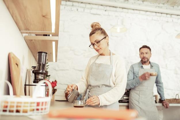 仕事で思いやり。カウンターの近くに立ってコーヒーカップにミルクを注ぐバリスタの想いがいっぱい。