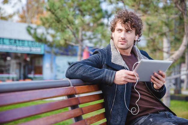 Thoughtful attractive curly handsome man in black jacket listening to music from tablet sitting on the bench in the park