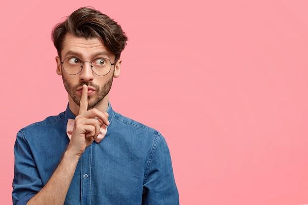 思いやりのある魅力的なヨーロッパの男性は、人差し指を口に当て、静けさのサインを作り、沈黙を要求し、秘密を守るように頼み、ピンクの壁にポーズをとる