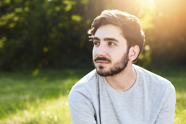 Thoughtful attractive male with dark mustache and beard looking aside into distance dreaming about something pleasant while relaxing