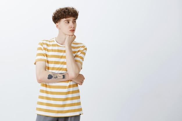 Задумчивый привлекательный парень-подросток позирует у белой стены