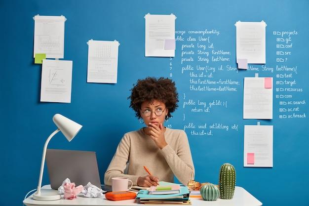 안경에 사려 깊은 매력적인 여성이 일기에 목표 목록을 작성하고 개인 주최자에 메모를 작성합니다.