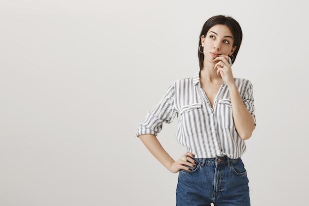Donna attraente premurosa che guarda a sinistra la pubblicità, pensa o fa la scelta