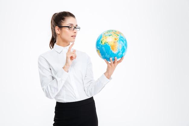 Задумчивая привлекательная молодая деловая женщина держит глобус и думает