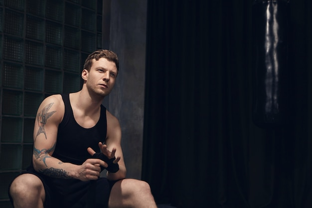Thoughtful attractive young european man wearing sleeveless shirt and shorts wrapping boxing bandages