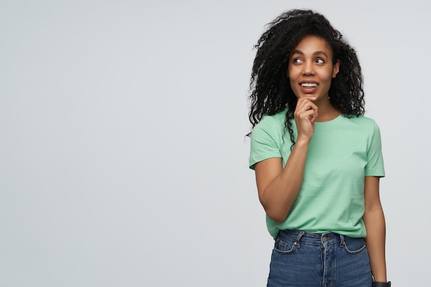 Thoughtful attractive young woman in mint tshirt touching her curly hair using smartphone and thinking isolated over gray wall