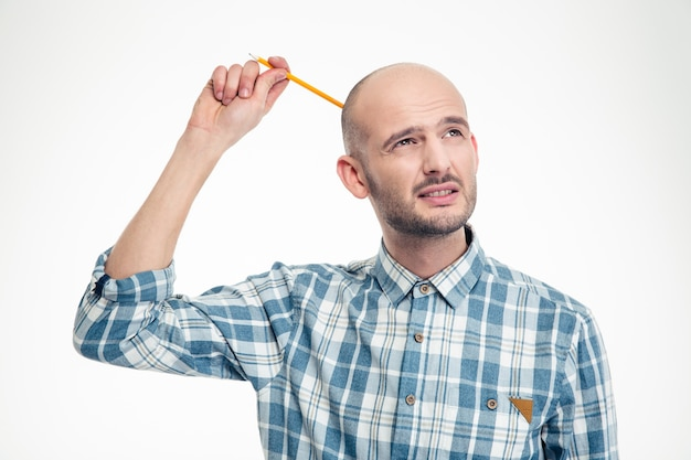 Thoughtful attrative young man scratching his head by pensil over white wall