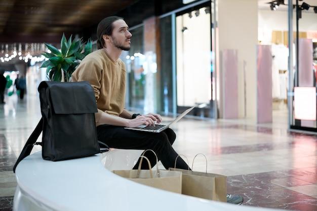 사려 깊은 수염 프리랜서 디자이너는 쇼핑 센터에서 즉시 작업합니다.
