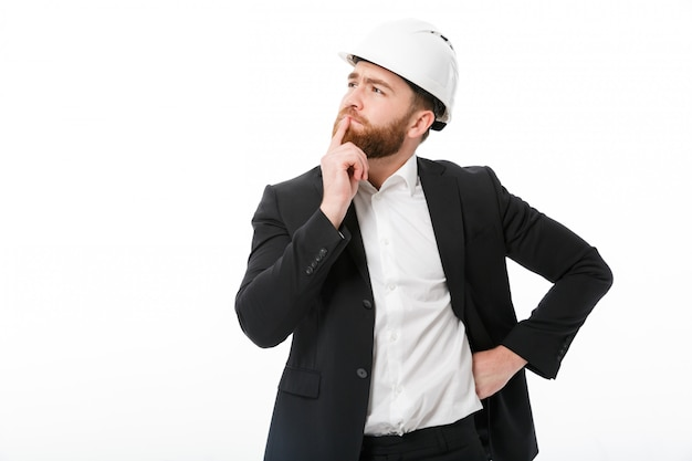 Thoughtful bearded business man in protective helmet looking away