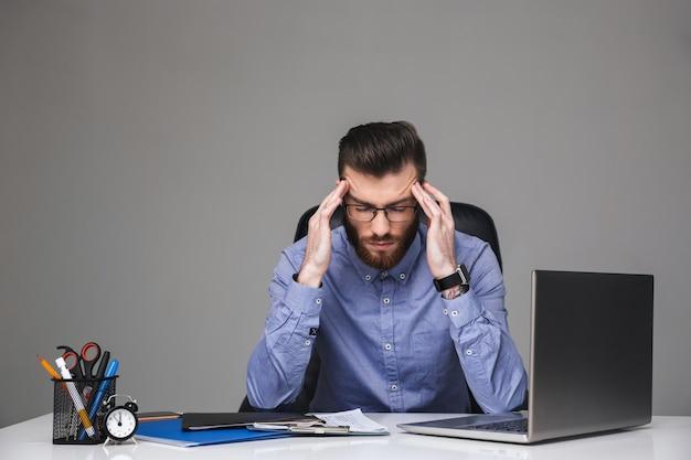 Вдумчивый бородатый элегантный мужчина в очках держит голову, сидя за столом в офисе