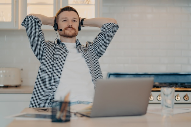 Thoughtful bearded male freelancer sits in relaxed pose takes break after working online wears headset with microphone listens educational webinar gets remote education uses new computer app
