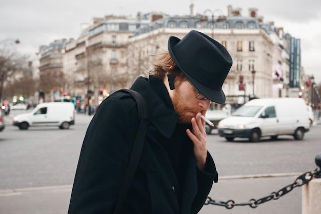 Thoughtful bearded man wearing hat smoking