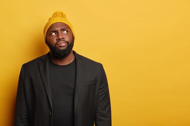 Riflessivo uomo barbuto con pelle scura, ricorda le informazioni in mente, indossa un cappello lavorato a maglia e abiti da cerimonia neri