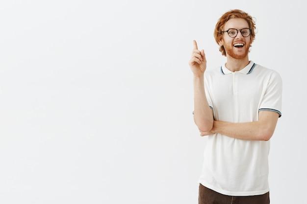 眼鏡をかけて白い壁にポーズをとる思いやりのあるひげを生やした赤毛の男
