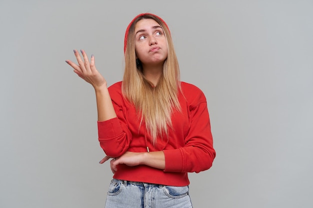 Thoughtful beautiful blonde young woman with freckles in red hoodie looking away and holding empty space on palm over gray wall