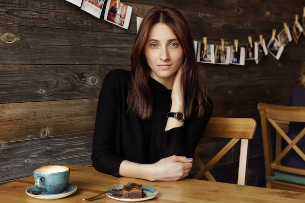 Thoughtful beautiful brunette female wearing elegant black dress and wrist watch touching neck while enjoying nice time alone during coffee break, sitting at cafe table with mug and dessert on it
