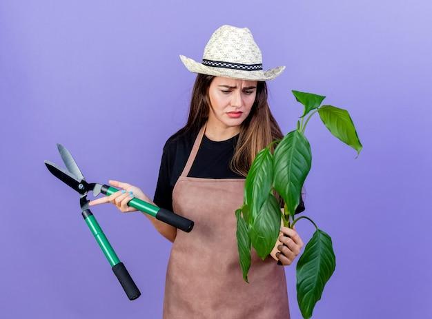 Premurosa bella ragazza giardiniere in uniforme che indossa cappello da giardinaggio tenendo i clippers e guardando la pianta in mano isolata sul blu