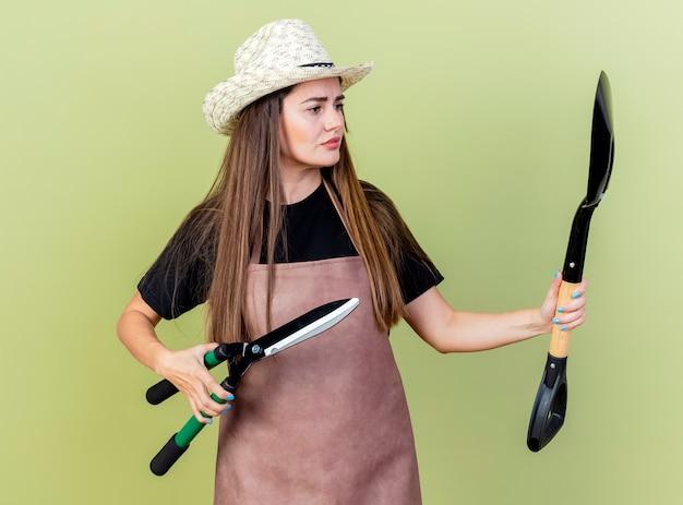 Premurosa bella ragazza giardiniere in uniforme che indossa cappello da giardinaggio holding clippers e guardando la vanga in mano isolata su verde oliva