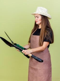 Premurosa bella ragazza giardiniere in uniforme che indossa il cappello da giardinaggio tenendo e guardando i clippers con vanga isolato su verde oliva