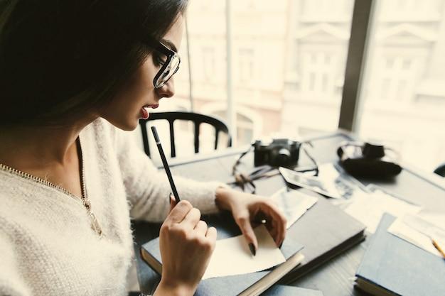 思いやりのある美しい女性がカフェに座っていくつかのメモを作る