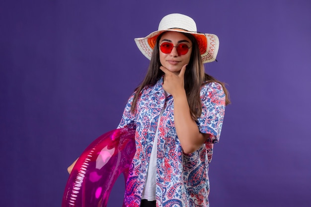 夏の帽子と赤いサングラスを身に着けている思いやりのある美しい女性分離の紫色の背景をあごの思考に手でカメラ立って見てインフレータブルリングを保持