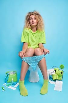 Premurosa bella donna con i capelli ricci si siede comodamente sul water indossa maglietta verde pantaloni di pizzo e calzini defeca in bagno pensa a qualcosa di isolato sul muro blu