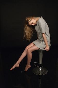 스튜디오에서 긴 금발 머리와 회색 드레스에 사려 깊은 아름 다운 젊은 백인 마른 여자