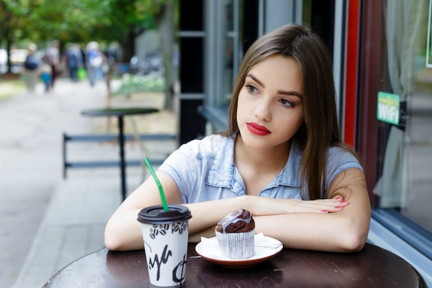 Thoughtful beautiful  young woman in outdoor cafe with coffee and muffin