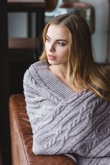 Задумчивая красивая молодая женщина, сидящая на диване, завернутая в серое вязаное покрывало