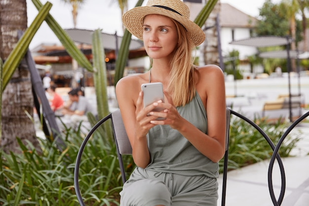 Thoughtful beautiful young woman thinks about something while recreate in outdoor cafe with smart phone during summer day, looks away, connected to wireless internet for online communication