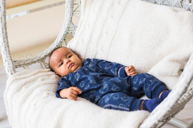 黄色がかった色の毛布の上に横たわっているヒスパニック系とアフリカ系アメリカ人の幼児の思慮深い異人種間のミックス