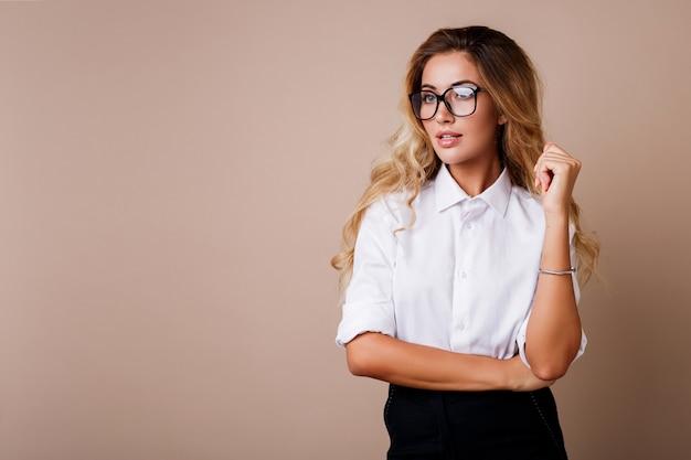 Заботливая белокурая женщина представляя изолят на бежевой стене. стильная повседневная рабочая одежда.
