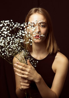Thoughtful blond woman with white flowers