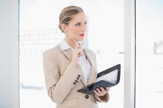 Thoughtful blonde businesswoman holding datebook