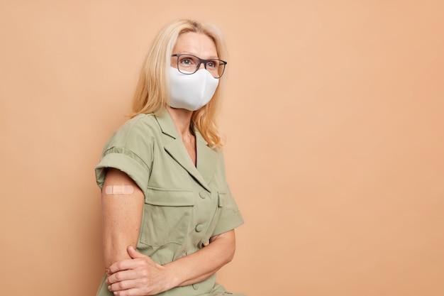 사려 깊은 금발의 중년 여성은 베이지색 벽에 격리된 코로나바이러스 주사 후 팔을 보여주는 보호 마스크 안경을 착용합니다