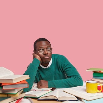 Thoughtful bored black man holds hand on cheek, looks upwards, wears green sweater, optical glasses, thinks about creating new project work