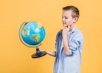 Вдумчивый мальчик, глядя на руку глобус стоял на желтом фоне