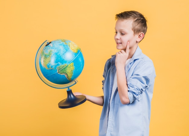 Thoughtful boy looking at hand globe standing against yellow background