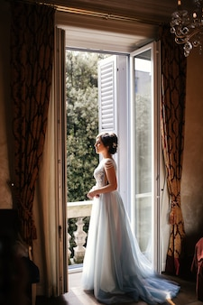 Thoughtful bride stands before an open window in the morning