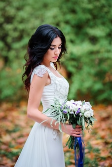 Thoughtful brunette bride poses with pretty wedding bouquet on fallen leaves