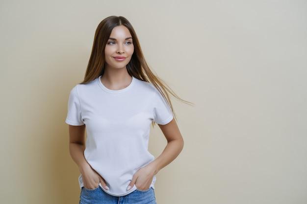 Thoughtful brunette woman looks aside, wears casual white t shirt, keeps hands in pockets, looks aside