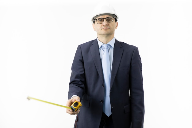 Thoughtful builder wearing white helmet holds tape measure looks at camera