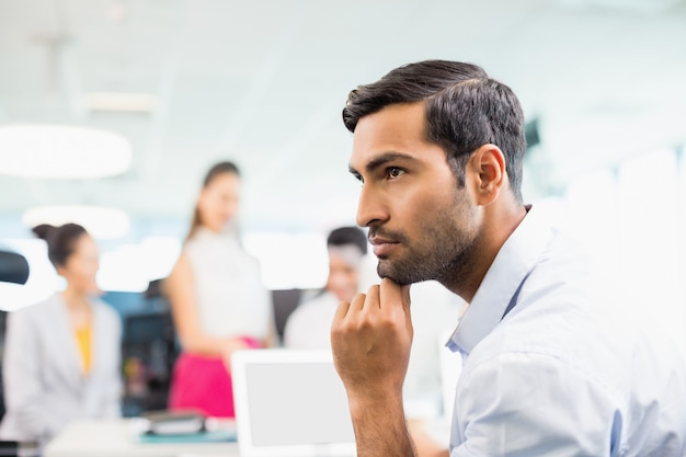 Thoughtful business executive sitting at desk