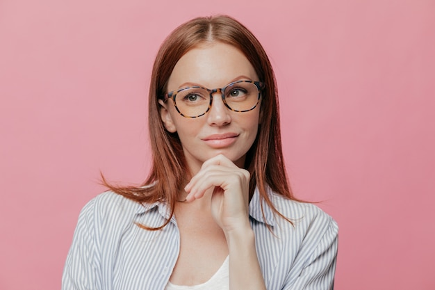 Thoughtful business lady holds chin, looks aside with pensive expression, wears spectacles